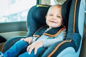 תינוק מחייך יושב במושב בטיחות ברכב