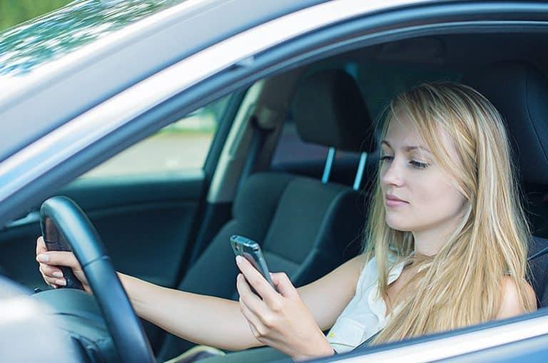 בחורה צעירה מסתכל בטלפון הנייד כשהיא נוהגת