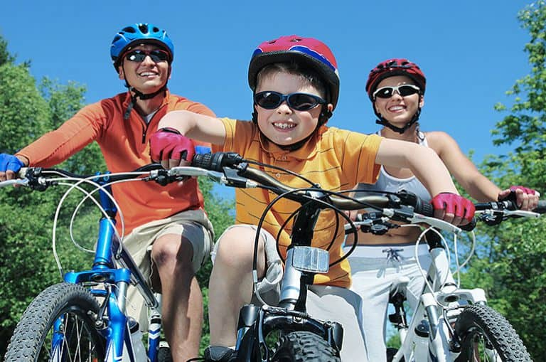 משפחה רוכבת אל אופניים כשהם חובשים קסדות ומשקפי שמש