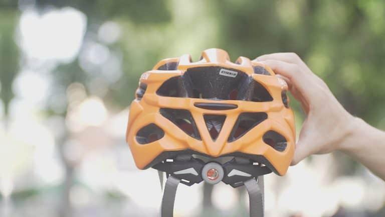 יד מחזיקה קסדת אופניים בצבע כתום