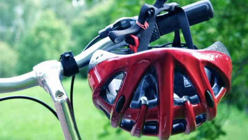 קסדה אדומה תלויה על כידון אופניים