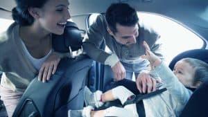 זוג הורים מחייכים לילד במושב בטיחות ברכב
