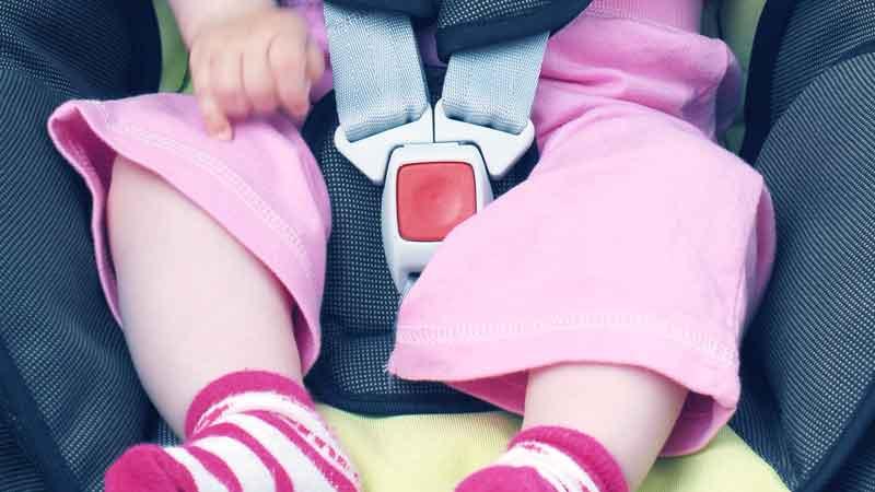 ילדה יושבת במושב בטיחות עם חגורה