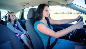 אמא וילדה נוסעים ברכב מחייכות