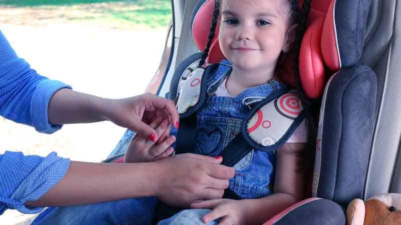 ידיים מתקינות חגורה על מושב בטיחות של ילדה מחייכת במושב האחורי