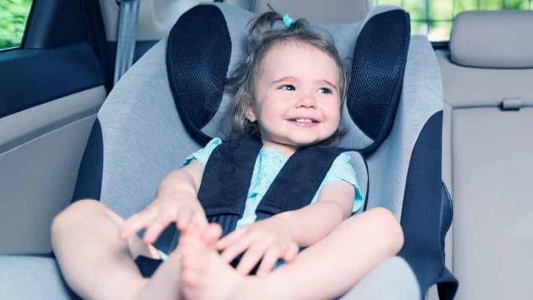 ילד במושב בטיחות מחייך
