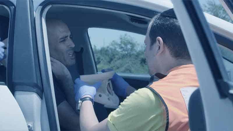 חובש של איחוד הצלה עוזר לנפגע צוואר בתאונה