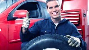 מוסכניק מחייך מחזיק גלגל של רכב מרים אגודל