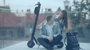 בני זוג יושבים ליד קורקינט חשמלי