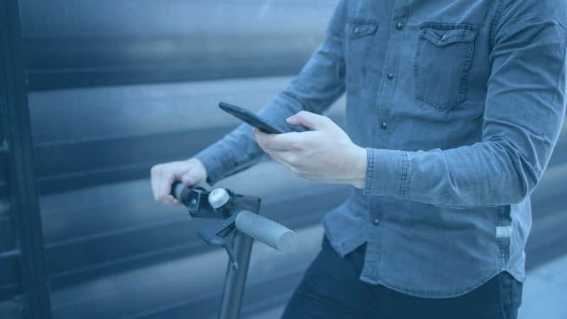 בחור מחזיק טלפון נייד וקורקינט חשמלי