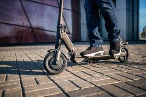 רגליים בנעלי ספורט על קורקינט חשמלי