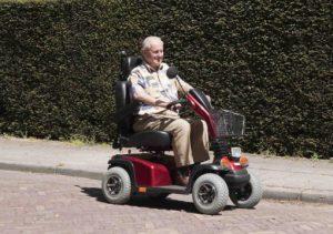 אדם מבוגר מחייך נוסע בקלנועית