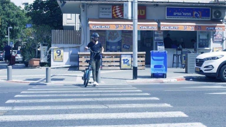 רוכב אופניים חוצה במעבר חצייה כשהוא מוביל את האופניים לצידו