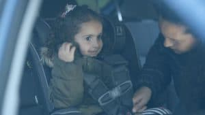 ילדה במושב בטיחות עם מעיל