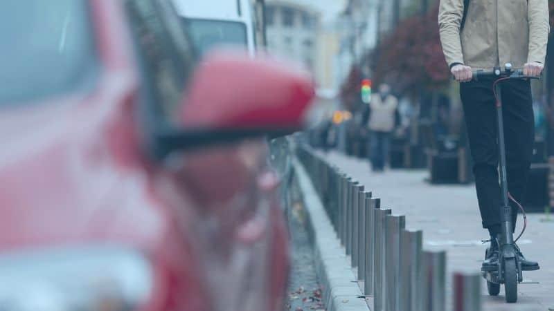 רוכב קורקינט לצד מכוניות בכביש